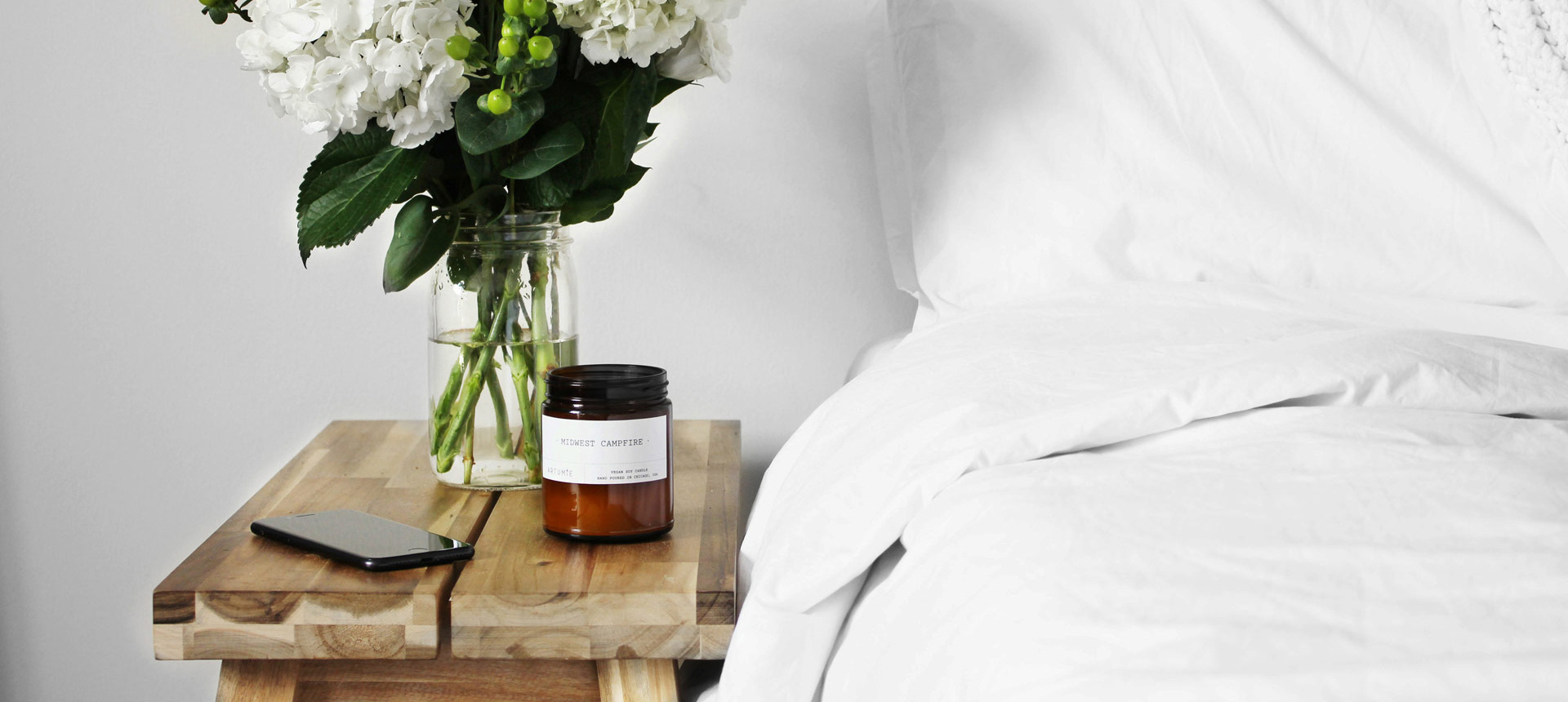 Comfortable bed with flowers and candle on side table