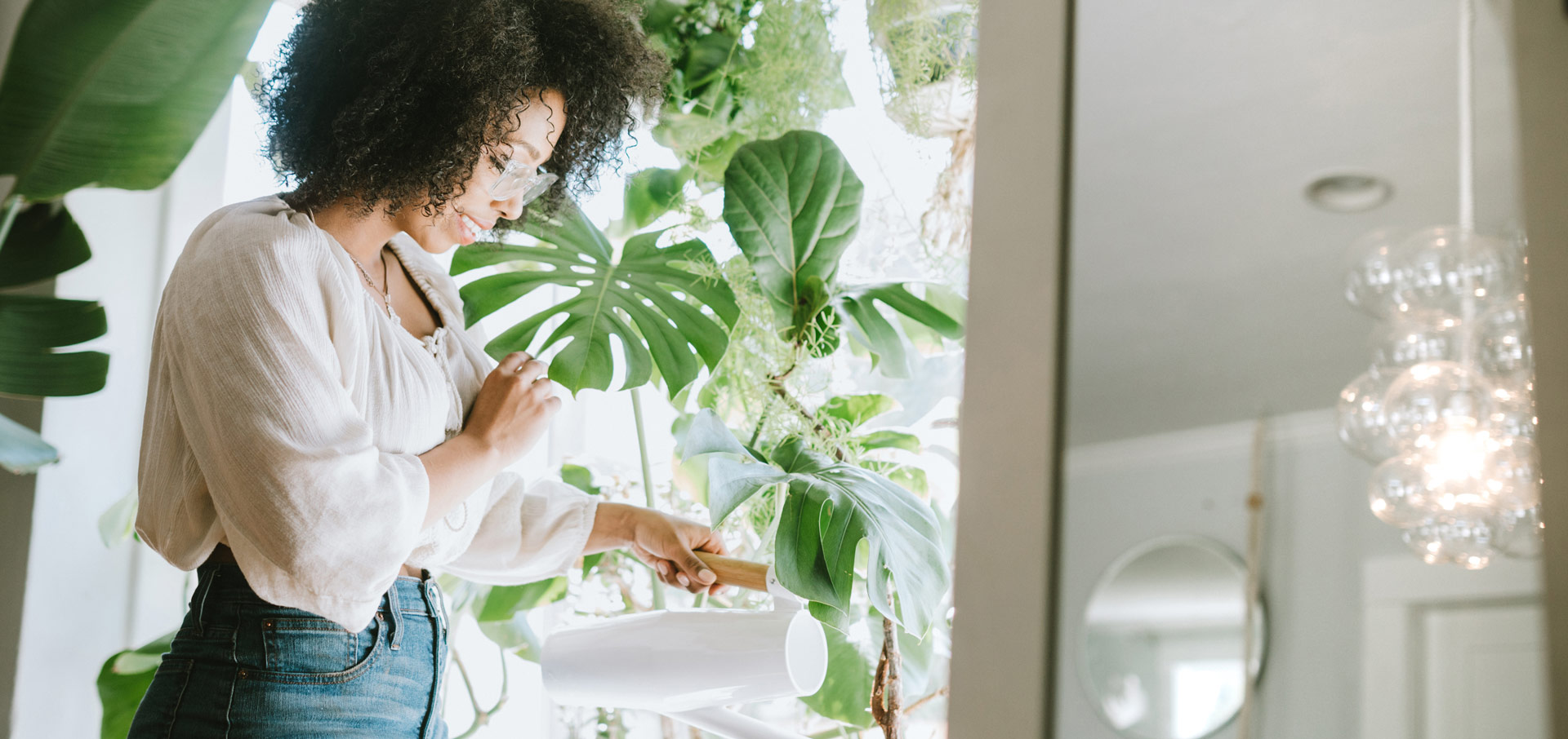 Woman watering collection of tropical plants