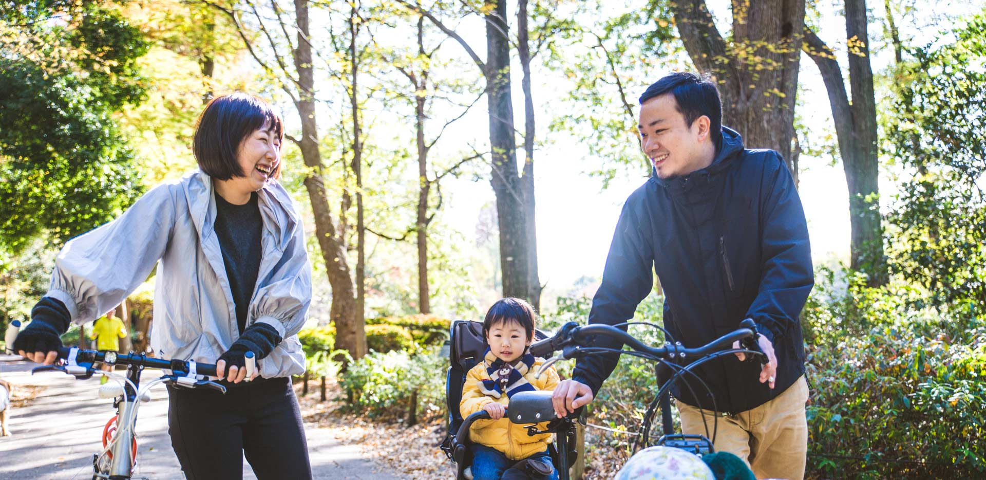 Family of three walking bikes on a wooded trails
